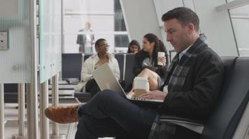 Businessman working on laptop at airport video