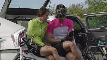 Two cyclists taking break and looking at maps on digital tablet.  Fully released for commercial use. video