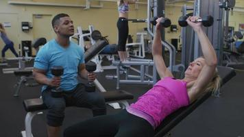 Woman lifting weights with trainer at gym video