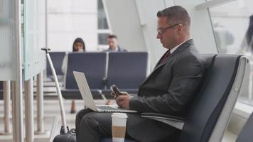 Businessman using laptop at airport video
