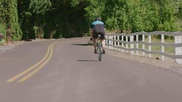 Cyclist pedaling down country road.  Fully released for commercial use. video