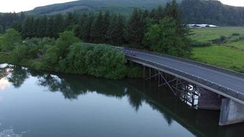 Aerial view of a group of cyclists going over bridge.  Fully released for commercial use. video