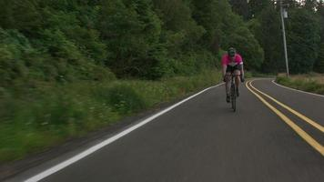Tracking shot of a male cyclist on country road.  Fully released for commercial use. video