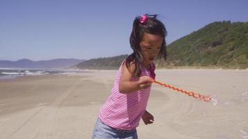 junges Mädchen spielt mit Blasen am Strand video