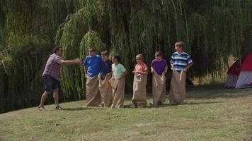 crianças no acampamento de verão na corrida de sacos video