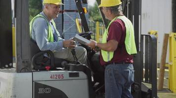 motorista de caminhão e motorista de empilhadeira conversam na instalação de transporte. totalmente liberado para uso comercial. video
