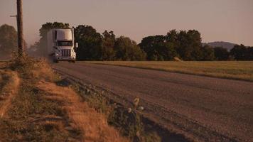 semi lastbil som kör ner dammig väg vid solnedgången. helt släppt för kommersiellt bruk. video