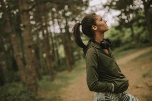 Hermosa joven corredora escuchando música y tomando un descanso después de trotar en un bosque foto