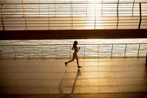 Mujer joven haciendo ejercicio para correr por el paseo fluvial foto