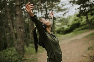 Mujer joven con auriculares predicando sus brazos en el bosque porque le gusta entrenar al aire libre foto