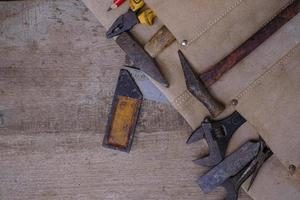 Collection of woodworking old hand tools in leather apron on a rough wooden workbench photo