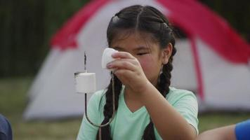 Young girl at summer camp eating a marshmallow video