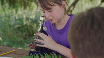 Girl at outdoor school looking through microscope video