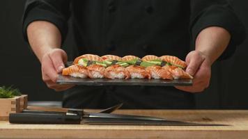 chef tenant une assiette de sushis frais video