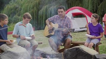 Kids at summer camp by campfire with leader playing guitar video
