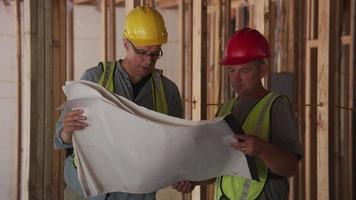 trabajadores de la construcción mirando planes video