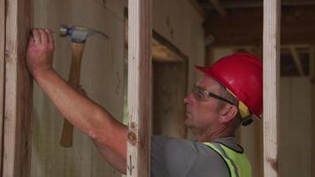 Construction worker nailing wall studs video