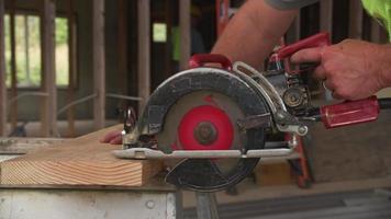 Primer plano de un trabajador de la construcción cortando con sierra circular video