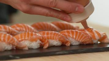 Chef adds sauce to top of sushi, closeup video