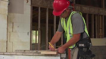 Trabajador de la construcción cortando con sierra circular video