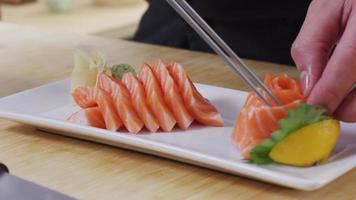 Sushi chef placing Salmon fish onto tray video