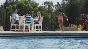 Girl jumping into backyard pool video