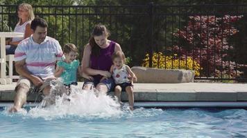 Family splashing feet in backyard pool video