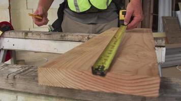 Trabajador de la construcción midiendo y marcando madera. video