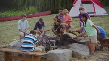 Kids at summer camp roasting marshmallows around campfire video