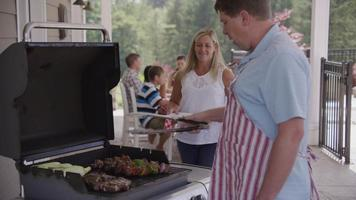 Serving food from grill at backyard barbeque video