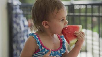 Young girl eating watermelon at backyard barbeque video