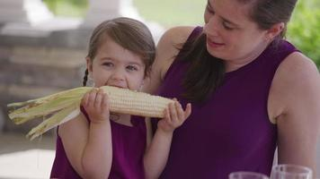 Young girl eating corn at backyard barbeque video