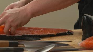 chef de sushi tranchant du poisson saumon video