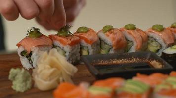 le chef ajoute une garniture aux rouleaux de sushi video