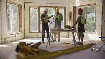 Tres trabajadores de la construcción mirando planos en un sitio de construcción comercial video
