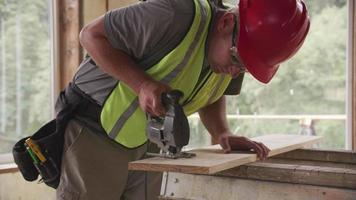 Construction worker cutting wood with jigsaw video