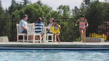 Girls jumping into backyard pool in slow motion video
