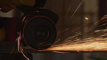 Construction worker grinding metal and making sparks, closeup video