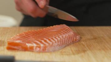 Sushi chef slicing Salmon fish video