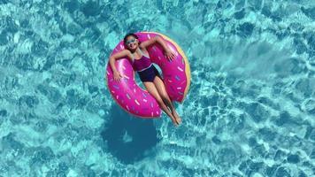 joven tendido en la cámara de aire en la piscina. video