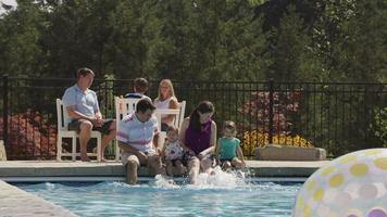 Family splashing feet in backyard pool, slow motion video