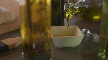 Olive oil is poured into dish video