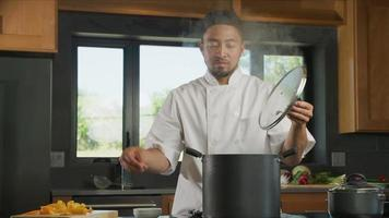 Chef drops seasoning into pot on stove video