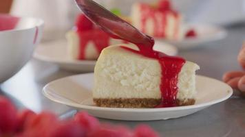 Pouring berry sauce onto slice of cheesecake video