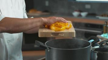 Chef drops peppers into pot in super slow motion, shot with Phantom Flex 4K camera. video