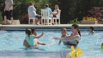 Family playing and splashing in backyard pool video