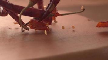 chiles cayendo sobre la superficie de madera en cámara super lenta. filmado en cámara fantasma flex 4k de alta velocidad. video