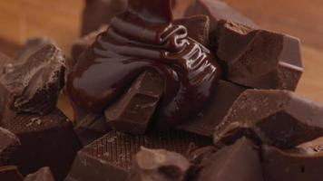 Melted chocolate pouring over chunks of chocolate video