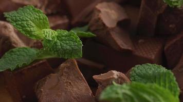 Chunks of chocolate with mint leaves, close-up video