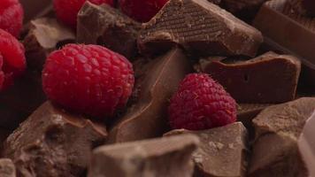 Chunks of chocolate with fresh red raspberries video